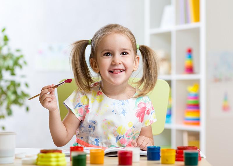 Lächelndes Mädchen mit Pinsel in der Hand und vielen Farbtöpfen am Tisch
