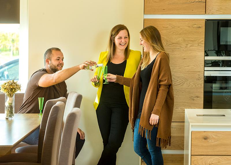 Ein junger Mann und zwei junge Frauen trinken Sekt in einem von der Malerei Zinkl gestalteten Raum