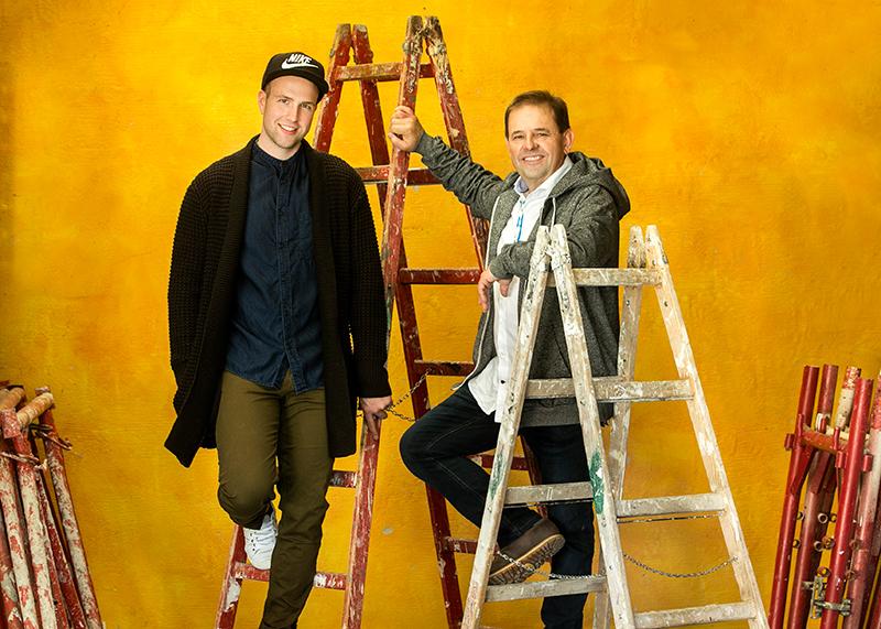 Team Zinkl - Manuel und Robert Zinkl mit Stehleitern vor einer gelben Wand